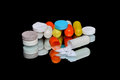 A pile of medicines lot different drugs on the black background with reflection Stock Image
