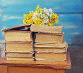 Pile of old books with a bouquet of yellow flowers Royalty Free Stock Photo