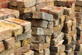 Pile of old bricks gathered from a fallen wall in the garden Stock Photography