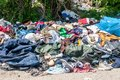 Image : Pile of old clothes and shoes dumped on the grass as junk and garbage, littering and polluting the environment   striped