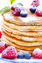Pile of pancakes with blueberries and raspberries sprinkled with Royalty Free Stock Photo