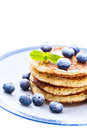 Pile of pancakes with blueberries sprinkled with icing sugar Royalty Free Stock Photo