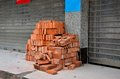 Pile of red bricks ready for construction a traditional rests on a pavement to be used impending works Royalty Free Stock Photos