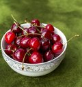 Pile of red cherries in ceramic bowl on green grass