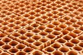 Pile of red hollow bricks with large holes forming a repetition geometric pattern Royalty Free Stock Photo