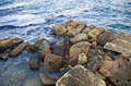 A pile of rocks compiles a land tongue invading sea water s territory Stock Image