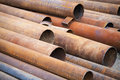 Pile of rusted industrial steel pipes lay on the ground Stock Photo