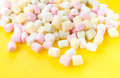 A pile of small colored puffy marshmallows on bright yellow ba background close up top view Royalty Free Stock Photography