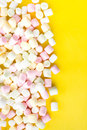 A pile of small colored puffy marshmallows on bright yellow ba background close up top view Stock Image