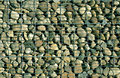 Pile of stones behind metal grid. Royalty Free Stock Photo
