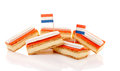 Pile traditional dutch pastry called tompouce flags over white background Stock Image