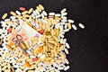Pile of vitamin, mineral and herbal supplements with a fifty euro bill Royalty Free Stock Photo