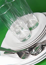 Pile of white plates, glasses, forks, spoons. Stock Image