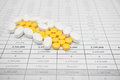 Pile of white and yellow pills for painkiller on finance report Stock Images