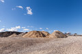 Piles of gravel at construction site under bright blue sky sand and Stock Photos