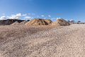 Piles of gravel at construction site under bright blue sky sand and Royalty Free Stock Photos
