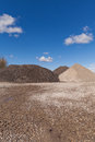 Piles of gravel at construction site under bright blue sky sand and Royalty Free Stock Images
