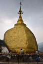 Pilgrims praying and pasting gold foils together onto golden rock at the Kyaiktiyo Pagoda, Myanmar with row of small bells Royalty Free Stock Photo