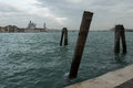 Pilings in the canal along quay of giudecca with a view to venice Royalty Free Stock Photography
