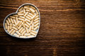 Pill heart shaped box wooden surface Royalty Free Stock Photography