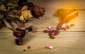the Pill spilling out of brown color pill bottle with dried rose Royalty Free Stock Photo