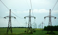 Pillars of line power electricity on green field Royalty Free Stock Photo