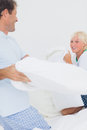Pillow fight between and father and his son in the bedroom Royalty Free Stock Photos