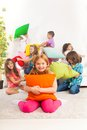 Pillow fight with kids happy smiling little girl hugging large group of her friends fighting on the coach Royalty Free Stock Photos