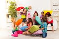 Pillow fight large group of kids boys and girls playing in the living room hitting each other with colorful pillows Stock Images