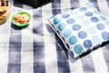 Pillow and snacks sitting on picnic blanket outside Stock Image