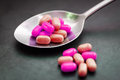 Pills or candy in spoon on dark background Stock Photos
