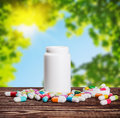 Pills of different colors and a bottle of medicine against Royalty Free Stock Photo