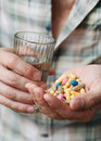 Pills and glass of water in the man hand Stock Photos