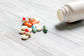 Pills and pill bottle on grey table background copyspace