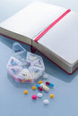 Pills planner with weekly medication capsules and note book Royalty Free Stock Photo