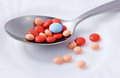 Pills on silver spoon concept of healthy and or artificial diet where natural ingredients are replaced by medicine concept of Stock Image