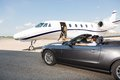 Pilot in convertible parked against private jet at airport terminal Stock Image