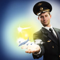 Pilot in the form of extending a hand to a flying airplane with sky clouds and sun Stock Images