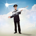Pilot in the form of extending a hand to a flying airplane with sky clouds and sun Royalty Free Stock Photo