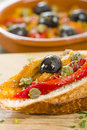 Pimientos asados tapas spanish roasted red pepper salad with olive oil vinegar garlic capers and black olives on crusty bread Stock Image