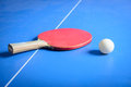 Pin pong ball and red paddle on blue board with Royalty Free Stock Image