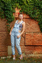 Pin up girl beautiful in denim overalls and a t shirt outdoors Stock Photos