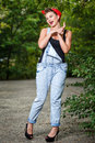 Pin up girl beautiful in denim overalls and a t shirt outdoors Royalty Free Stock Images