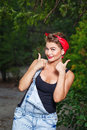 Pin up girl give thumbs up beautiful in denim overalls and a red bandana a Royalty Free Stock Photography
