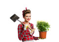 Pin-up girl holding flower pot with yellow daisies and spade Royalty Free Stock Photo