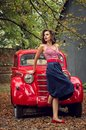 Pin-up girl posing on a red russian retro car background. A playful interested look is cast aside. Royalty Free Stock Photo