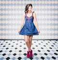 Pin up girl in retro style with old fashioned denim dress and shoes patterned interior Royalty Free Stock Photos