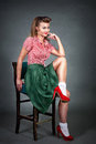 Pin-up girl sitting on a chair on a grey background dressed in a red blouse and green skirt on the feet white socks and red shoes Royalty Free Stock Photo