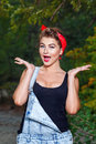 Pin up girl surprise beautiful in denim overalls and a red bandana very surprised Royalty Free Stock Images