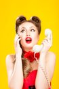 Pin up girl talking on retro telephone yellow background Royalty Free Stock Image
